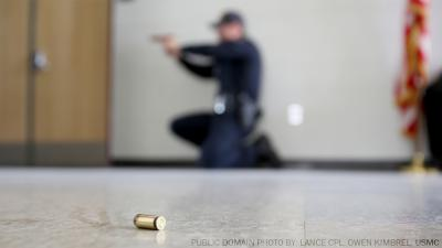Photo of officer crouching with gun and bullet in foreground