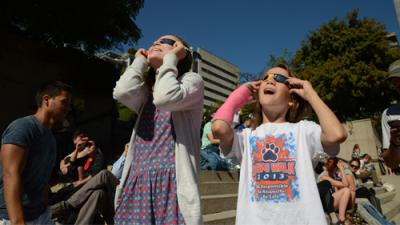 Photo of two girls watching eclipse through solar glasses with awed expressions