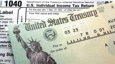 Photo of United States treasury check laid over 1040 federal tax return.