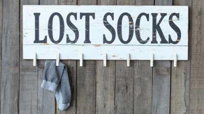 Photo of a painted wall sign with clothespins for lost socks.