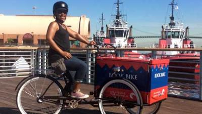 Photo of smiling woman on a bike with a book box on a pier