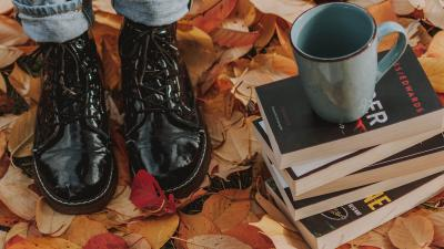 Closeup of person in shiny black boots standing next to books on fall leaves.
