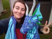 Photo of the artist with a blue soft-sculpture dragon