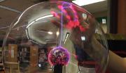Photo of a hand illuminated by a plasma ball.
