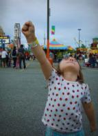 Photo of a girl making a triumphant fist at a county fair.