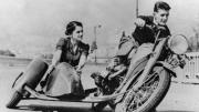 Man riding a motorcycle while a woman in the sidecar looks on affectionately.