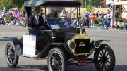 Couple driving vintage Model-T Ford in a parade.