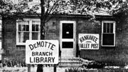 Photo of a building with signs for the Kanakee Valley Post and DeMotte Library.