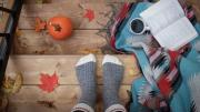 Person in gray socks standing above a book, blanket and fall leaves.