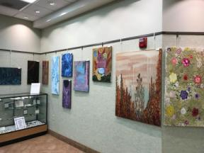 Photo of several paintings on the Wheatfield Library art wall.