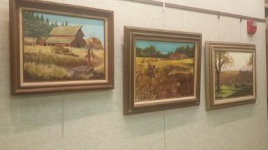 Photo of three framed farm-themed paintings, two with barns, one with sheep.