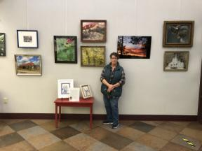 Photo of Claudia Pletting in front of her display on the Rensselaer art wall.