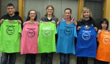 Teens holding stenciled t-shirts.