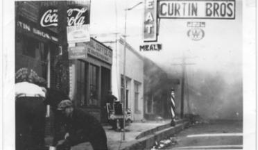 Photo of men with metal buckets in front of businesses while a fire rages.