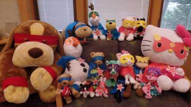 Stuffed animals wearing superhero costumes.