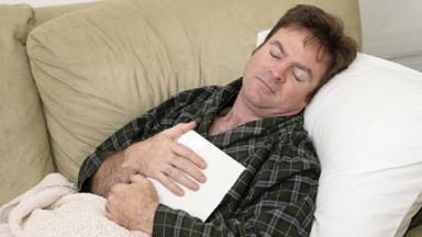 photo of man asleep on couch reading book