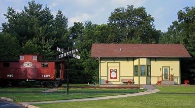 Photo of red train caboose parked next to yellow train depot.