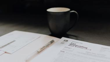 Photo of coffee cup with tax form