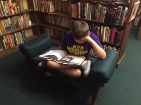 Photo of teen wearing KV shirt reading on cushioned chair in book shop.